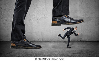 Businessman is running away from big foot on gray concrete background.