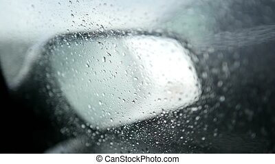 View of the road in the rearview mirror of a car on rainy...