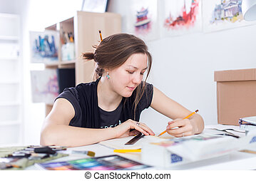 Young female artist drawing sketch using sketchbook with...