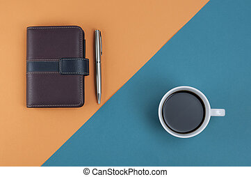 Note book pen and coffee on orange cross light blue pastel background,Top view,Flat lay.