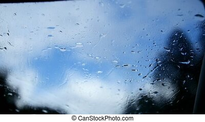 Autumn highway on a rainy day - defocused background. Moving waterdrops in the wipers of the windshield