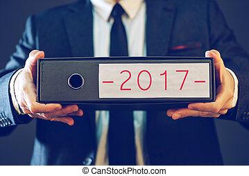 Businessman holding 2017 document ring binder folder with...