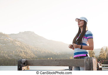 Young woman standing on a wooden lake pier and watching at...