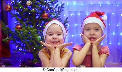 Two charming girl smiling and dancing in the evening of Christmas. In the background, lights and garlands of Christmas fir