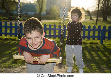 In the evening in the park on the playground boy riding on a...
