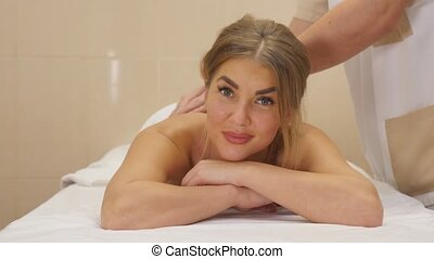 Beautiful blonde girl is looking at camera and smiling, lying on front while a massage therapist is massaging her back