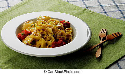 Delicious Meat Cappelletti with Tomato Sauce in White Plate...