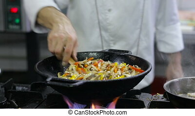 Chef frying vegetables and meat in a wok in the kitchen