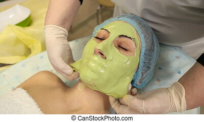 woman with green mask on her face in the beauty salon