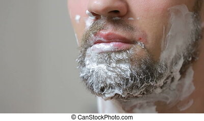 guy shaving off his beard with a razor in the bathroom and...