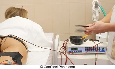Woman getting electrical muscle stimulation in spa.