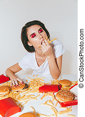 Pretty woman sitting at the table and eating french fries -...