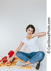Joyful woman eating french fries and burger on the table -...