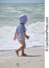 two-year-old boy run on the beach