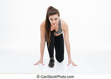 Young sports woman standing in start position for running -...
