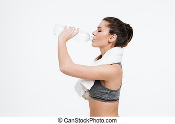 Woman drinking water from a bottle with towel around neck