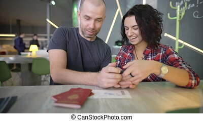 Young couple sitting at a table and looking at smartphone screen by clicking on it with their fingers. Man and woman reviewing their photos on the gadget while laughing and actively comment on them.