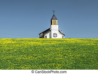 Small rural church in a field with yellow flowers