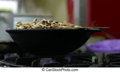 Mushrooms are fried in a wok in the kitchen.