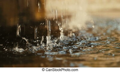 Close-up of the dripping water, in the sunlight. Golden...