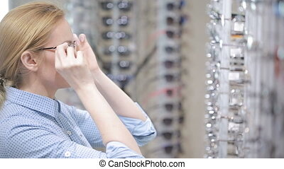 woman blond girl is choosing new eyeglasses in optics -...