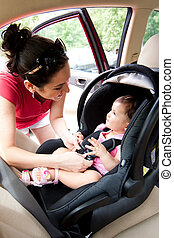 Baby in car seat for safety - Happy smiling mother placing...