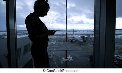 Silhouette of young fit girl standing near airport window and using her smartphone. Shapely young business woman waiting for her boarding near the gate with the window and plane in the background.