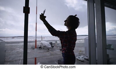 Beautiful brunette girl with short hair at the airport. She is happy. Since she was going on vacation and plans to travel is in a good mood. Standing panoramic window in the airport makes selfie