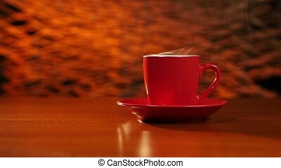 Cup of coffee is on the table on a red saucer - Cup of...