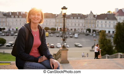 Woman tourist enjoying a view of a old city square - Smiling...