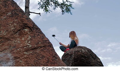 Woman taking self-portrait with phone in mountains - Young...