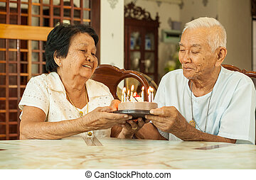 Asian senior couple holding a cake and smiling in living...