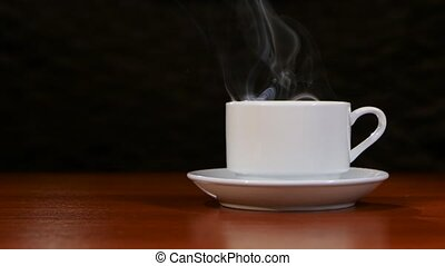 Cup of coffee costs on a wooden table and spreads a pleasant...