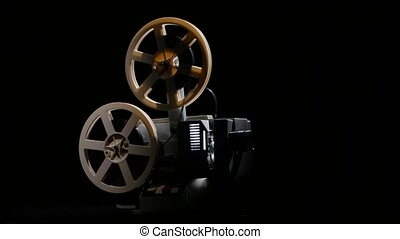 Retro projector showing film. Studio black background -...
