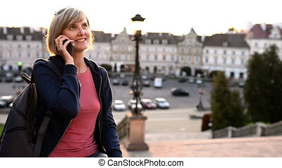 Woman sitting outdoors using smartphon - Smiling casual...