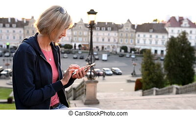 Woman sitting outdoors using smartphon - Closeup of a casual...