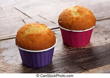 two muffins on a wood table