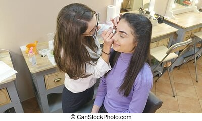 Make-up artist applying powder with a brush on model's...