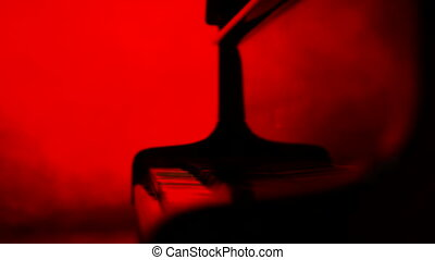 A pianist closes a lid to the piano, red background -...