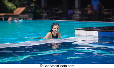 Young sexy woman in a good mood floats along the pool on a warm sunny day, swam to the side and starting to jump up and down, then raises his hands and fervently laughs