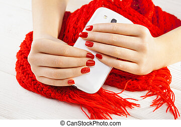 manicure with smartphone and red knitted scarf - red...