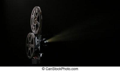 Dark studio. Projector illuminated by lights broadcasts a movies