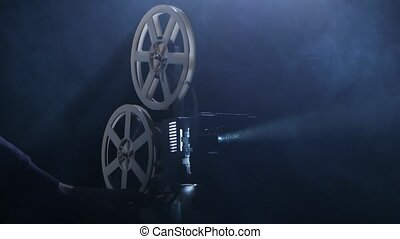 Projectionist includes projector. Dark background studio in...