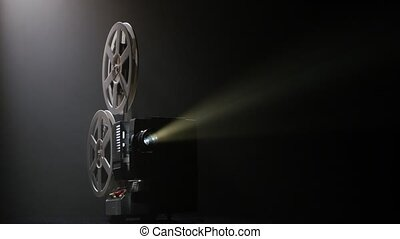 Projector illuminated by lights broadcasts a movies. Dark...