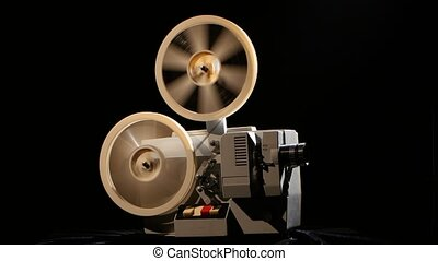 Projector. Rewinding the film from one the reel to another -...