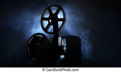 Old vintage movie projector, side view, smoke on black...