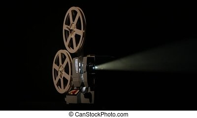 Shows movie in a projector. Black background