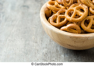 Salted pretzels in bowl on wooden background