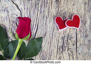 Red rose with two hearts on textured wood for valentine's...