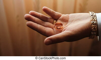 the hand squeezes wedding rings in a fist